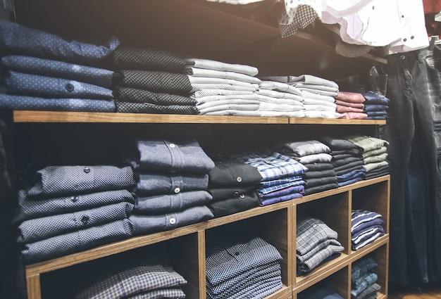Planken met kleren in winkel. tassen, pakken, broeken, overhemden en truien op de markt. winkeldag en verkoop. mode foto.