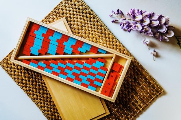 Planken van rode en blauwe houten montessori om het kind met visuele duidelijkheid, berekeningshandelingen te vergemakkelijken.