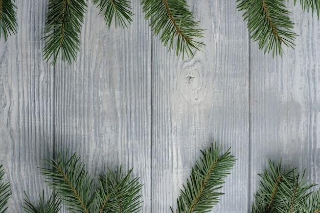 Plankoppervlak omlijst met dennentakken. nieuwjaar en kerstmis achtergrond.