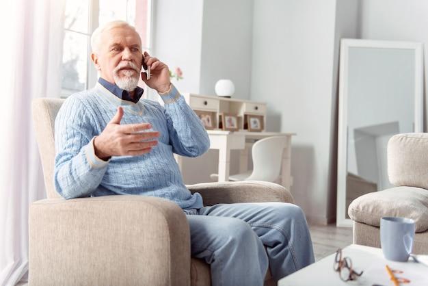 Plannen maken. aangename oudere man zit in de fauteuil in de woonkamer en praat aan de telefoon met zijn vriend, terwijl hij hun diner-arrangement bespreekt