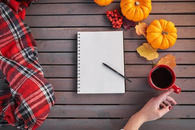 Plannen om lijst te doen. samenstelling van de herfststemming op een houten tafel. het jonge europese meisje met rode manicure op spijkers houdt in handen rode kop