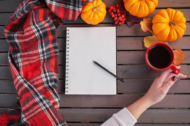 Plannen om lijst te doen. samenstelling van de herfststemming op een houten tafel. jong europees meisje met rode manicure op nagels houdt in handen rode kop, opwarming van de aarde drankje. gezellige sfeer