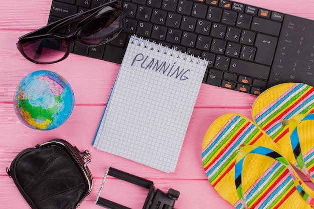 Plannen op een notitieboekje met een brillenportemonnee voor reizigersaccessoires en heldere slippers op een roze tafelbladachtergrond. bol en zwart toetsenbord.