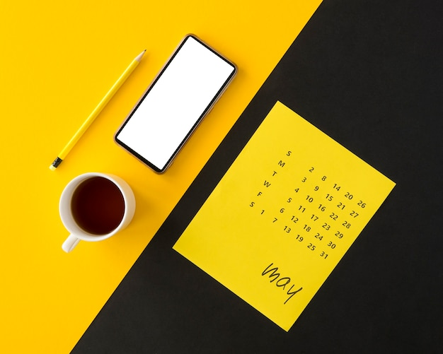 Plannerkalender op gele en zwarte achtergrond met koffie