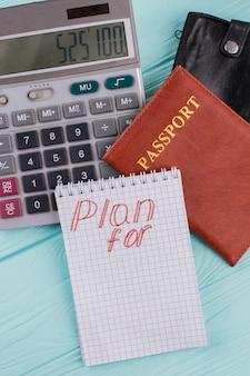 Planning en berekening van de kosten van vlucht of vakantie. rekenmachine paspoort portemonnee op blauwe achtergrond.
