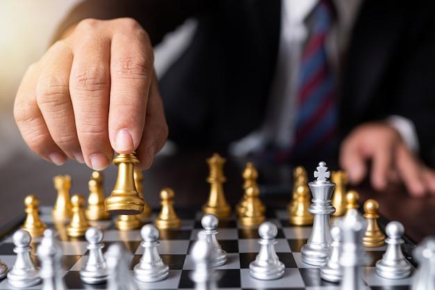 Planning en strategie van een succesvol concept van het bedrijfsconcurrentiebeheer, zakenman beweegt koning van schaak
