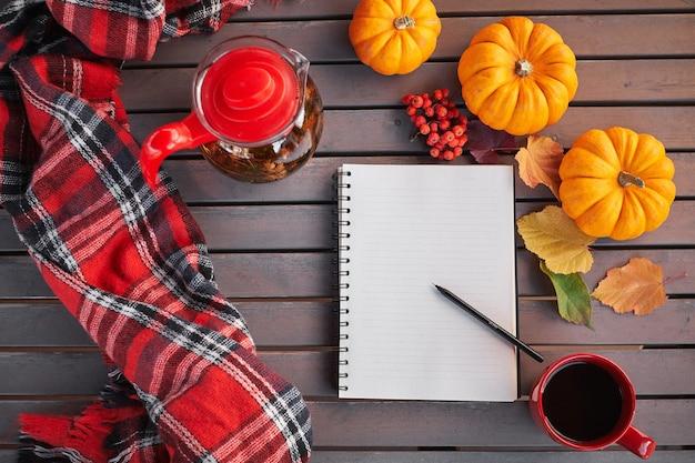 Planning om lijst te doen. samenstelling van de herfststemming op een houten tafel met pompoenen, lijsterbes en bladeren. open kladblok en zwarte koffie in de rode kop en op grijze houten tafel, drankje opwarmen. rode sjaal