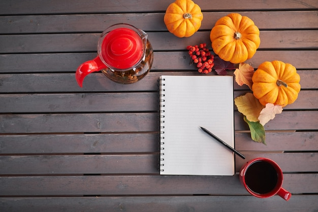 Planning om lijst te doen. samenstelling van de herfststemming op een houten tafel met pompoenen, lijsterbes en bladeren. open kladblok en zwarte koffie in de rode kop en op grijze houten tafel, drankje opwarmen