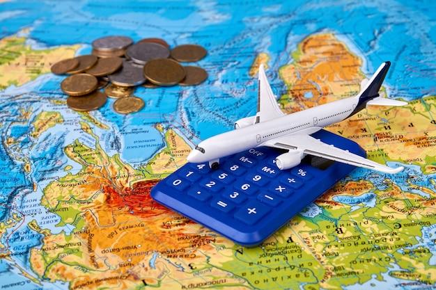 Planning reis concept met stapel munten en vliegtuig speelgoed
