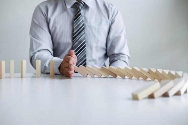 Planning risico en strategie in het bedrijfsleven, handbeeld zakenman stoppen en bescherming voor instorting van houten blokspel dat naar beneden valt dominostenen effect probleemoplossing van voorkomen