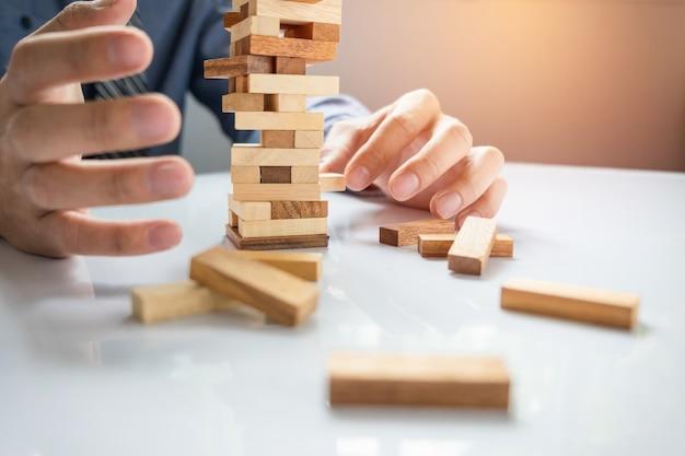 Planning, risico en strategie in het bedrijfsleven, zakenman gokken plakken houten blok op een toren