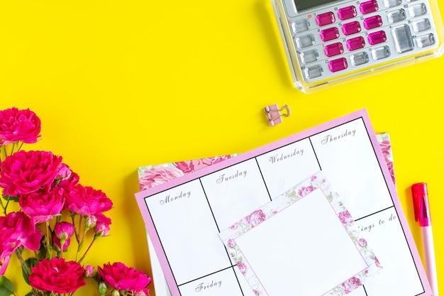 Planning van belangrijke dingen, roze schrijfinstrumenten op een gekleurde achtergrond. dingen om te doen. bovenaanzicht. kopieer ruimte.