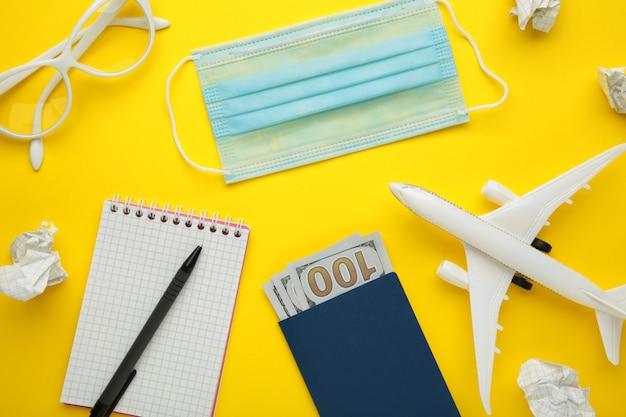 Planning van zomervakantie, toerisme en reis vintage achtergrond. reizigers notitieboekje met accessoires op geel. plat leggen.
