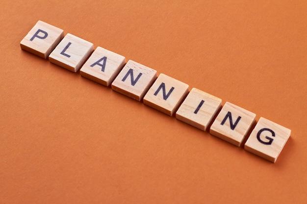 Planning woord op houten kubussen. alfabetblokken met letters geïsoleerd op een oranje achtergrond.