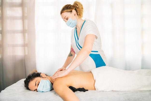 Plano lateral de mujer profesional de etnia caucãƒâ¡sica dando un masaje fisioterapeutico en la espalda llevando mascara de cara debido a la pandemia del coronavirus covid 19