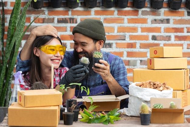 Plant online verkopen; koppels glimlachen tijdens het kweken van planten