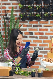 Plant online verkopen; vrouw die foto van plant door mobiele telefoon