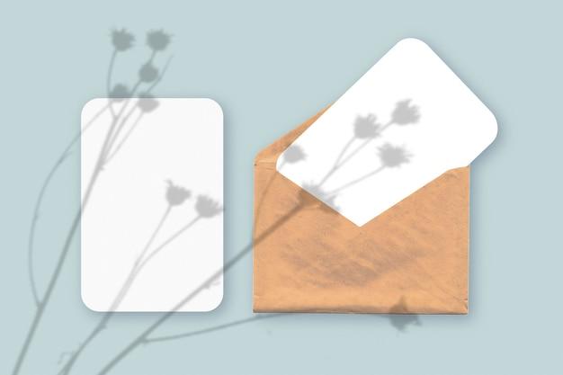 Plant schaduwen op envelop met twee vellen gestructureerd wit papier op een blauwe tafelachtergrond table