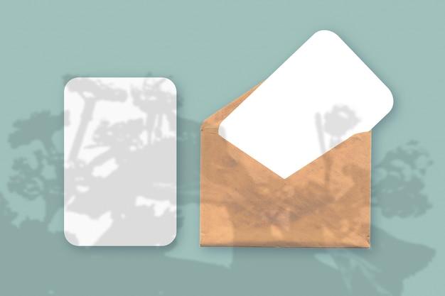 Plant schaduwen op envelop met twee vellen gestructureerd wit papier op een groene tafelachtergrond table