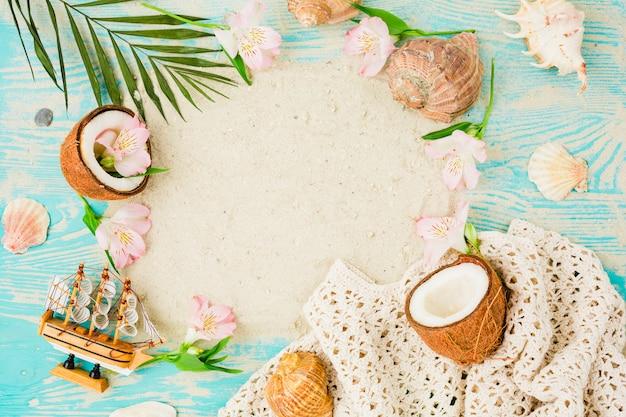 Plant verlaat in de buurt van kokosnoten en bloemen met schelpen aan boord