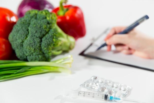Plantaardig dieet voeding of medicijnen concept. vrouwelijke persoon handen schrijven dieetplan, rijpe plantaardige samenstelling, drugs en spuit geïsoleerd op een witte achtergrond