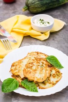 Plantaardig gefrituurde beignets van courgette en basilicumbladeren op een bord en zure roomsaus met greens in een kom op tafel