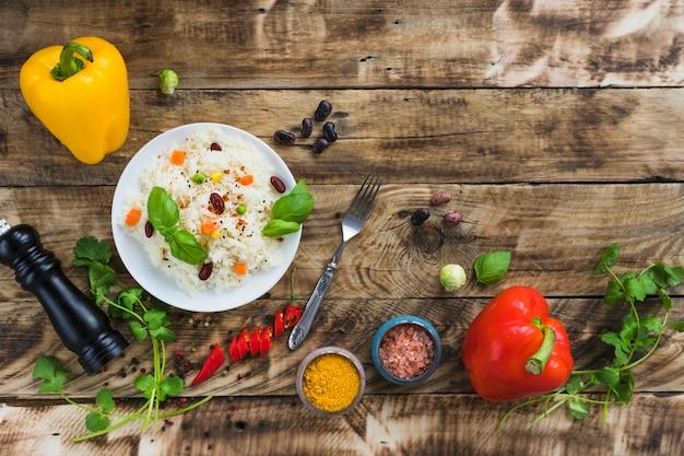 Plantaardige boonrijst en verse kleurrijke groenten over doorstane houten lijst
