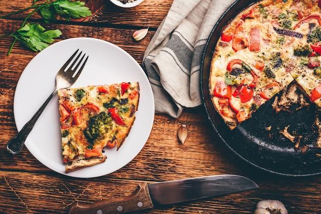 Plantaardige frittata met broccoli, rode paprika en rode ui op witte plaat en in een gietijzer. uitzicht van boven
