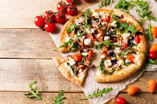 Plantaardige italiaanse pizza met tomaten op wodeen achtergrond, kopie ruimte, bovenaanzicht