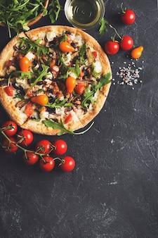 Plantaardige italiaanse pizza met tomaten op zwarte achtergrond, kopie ruimte, bovenaanzicht, verticaal