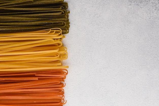 Plantaardige kleurrijke spaghetti grens. spinazie, tomaat en klassieke spaghetti op witte stenen achtergrond met kopie ruimte. spaghetti noedels.