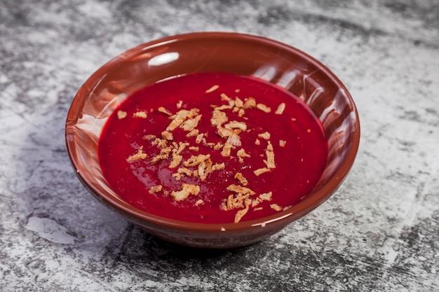 Plantaardige koude bieten romige soep met uienchips op een gestructureerde achtergrond. traditionele voedselcrème borsjtsoep in bruine plaat met uien. vegan soep borsjt tomaat, wortel, olijfolie. ruimte kopiëren