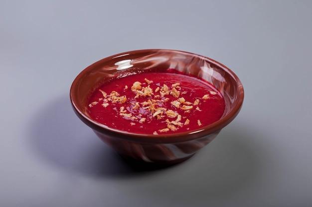 Plantaardige koude bieten romige soep met uienchips op lichtgrijze achtergrond. traditionele voedselcrème borsjtsoep in bruine plaat met uien. vegan soep borsjt tomaat, wortel, olijfolie. ruimte kopiëren