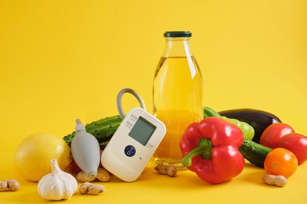 Plantaardige olie, groenten en bloeddrukmeter op een gele achtergrond. voeding en dieet voor hoge bloeddruk en hartaandoeningen