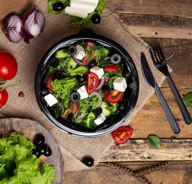 Plantaardige roka-salade met feta witte kaas, groene salade, tomaten en olijven.