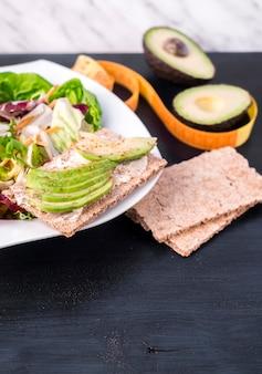 Plantaardige salade met avocado op knapperig brood op tafel