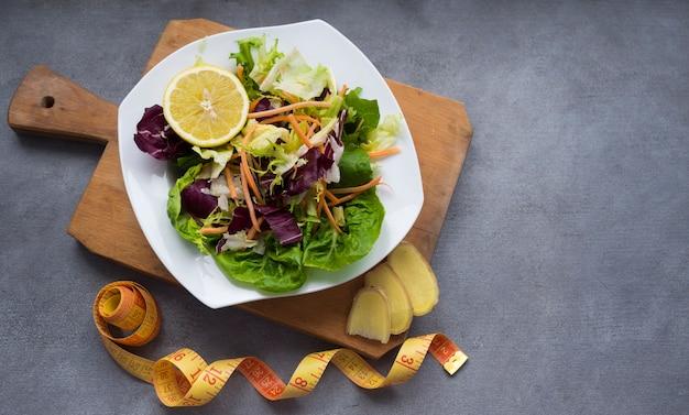 Plantaardige salade op houten bord met meetlint op tafel