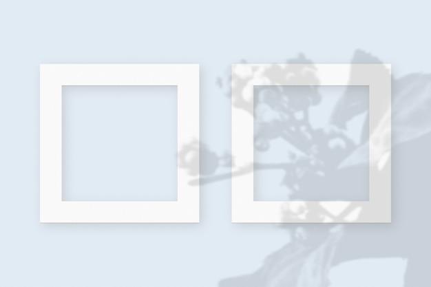 Plantaardige schaduwen gesuperponeerd op 2 vierkante frames van getextureerd wit papier op een blauwe tafelachtergrond