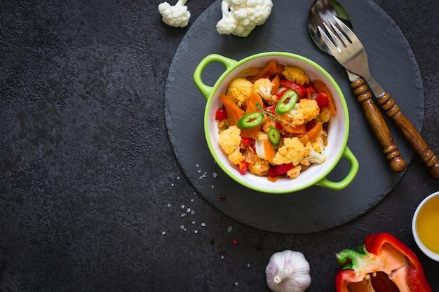 Plantaardige stoofpot van bloemkool, wortelen en tomaten op een zwarte achtergrond