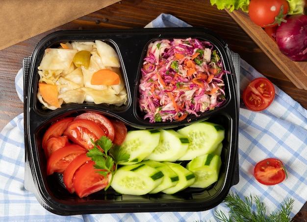 Plantaardige, tomaat komkommer salade afhaalmaaltijden met gemarineerde kool, turshu