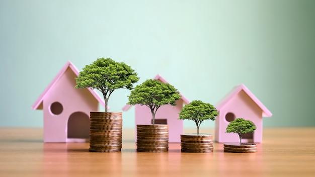 Planten die groeien op stapels munten en huismodellen simuleren ideeën voor investeringen in onroerend goed. woonkrediet en rentetarieven voor huizen