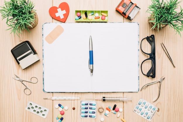 Planten en medische benodigdheden rond geopende notebook