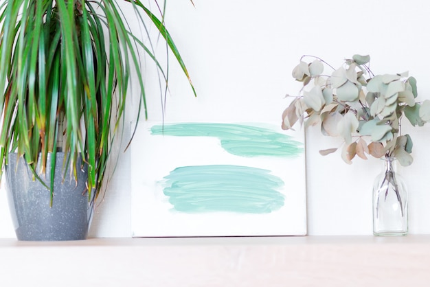 Plantensamenstelling van groene dracaena kamerplant in een pot, droge eucalyptus plant in glazen fles en geschilderde abstract beeld