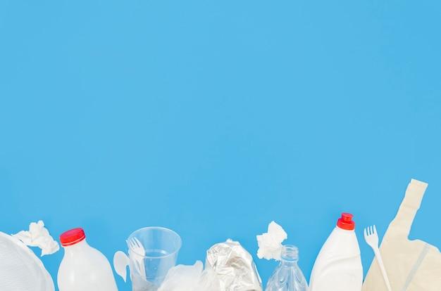 Plastic afval en verfrommeld papier gerangschikt aan de onderkant van blauwe achtergrond