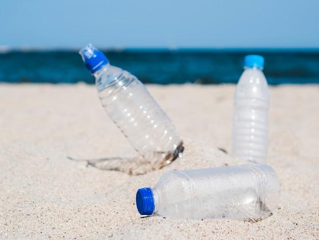 Plastic afval lege fles op zand bij strand