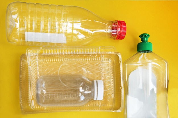 Plastic afval op een effen gele achtergrond. concept van afvalrecycling. milieubescherming.