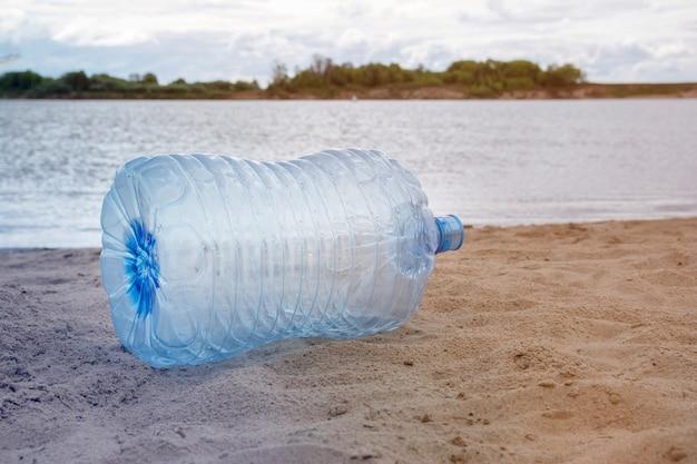 Plastic afval - plastic flessen die op het zand op de rivierbank liggen, het concept het recyclen van lege gebruikte plastic fles.
