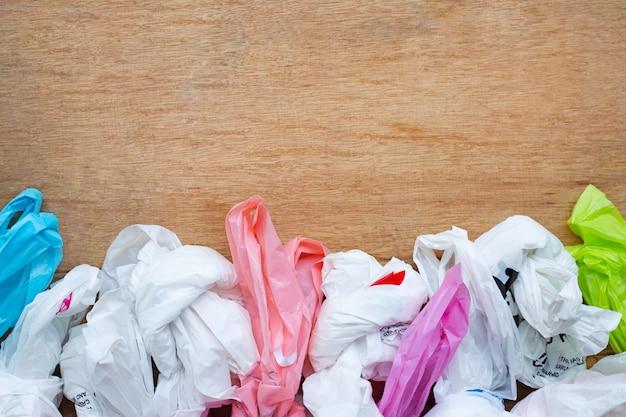 Plastic afval, plastic zakken op houten achtergrond.