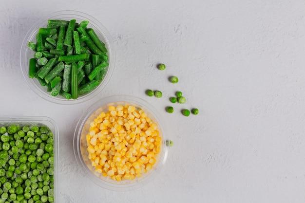 Plastic bak met verschillende biologische diepgevroren groenten op een witte betonnen tafel