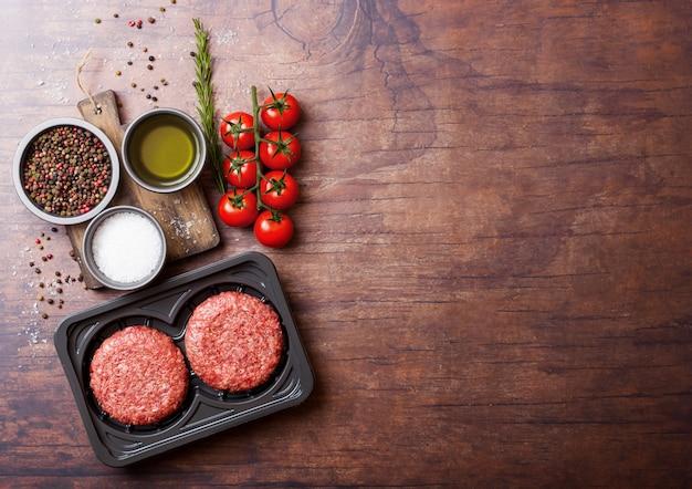 Plastic bakje met rauwe rundergehakt hamburgers met kruiden en specerijen. bovenaanzicht en.